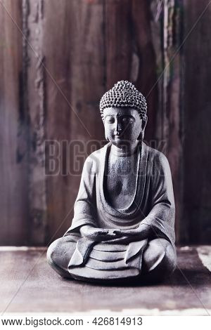 Meditating Buddha Statue On Wooden Background. Copy Space.