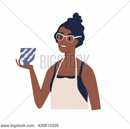 Young Happy Woman In Apron Looking And Admiring Ceramic Pot In Hand. Smiling Satisfied Female Potter