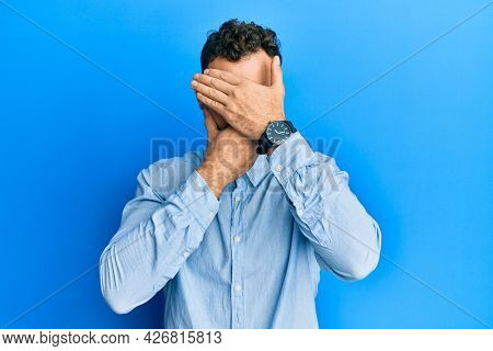 Young hispanic man wearing casual clothes and glasses covering eyes and mouth with hands, surprised and shocked. hiding emotion