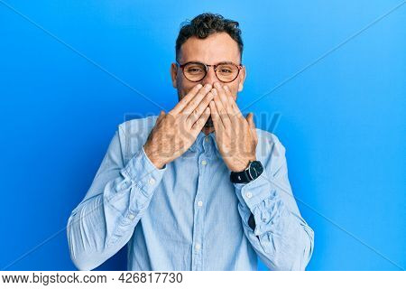 Young hispanic man wearing casual clothes and glasses laughing and embarrassed giggle covering mouth with hands, gossip and scandal concept