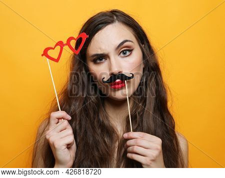 Party, emotion and people concept: Attractive playful young woman with long hair holding mustache and glasses on a stick