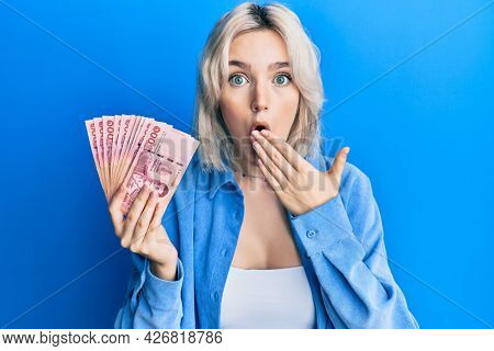 Young blonde girl holding thai baht banknotes covering mouth with hand, shocked and afraid for mistake. surprised expression