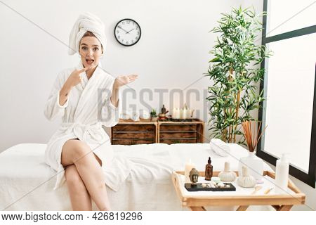 Young blonde woman wearing bathrobe at wellbeing spa amazed and smiling to the camera while presenting with hand and pointing with finger.