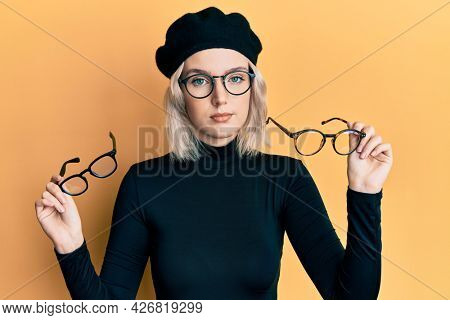 Young blonde girl wearing many glass over face relaxed with serious expression on face. simple and natural looking at the camera.