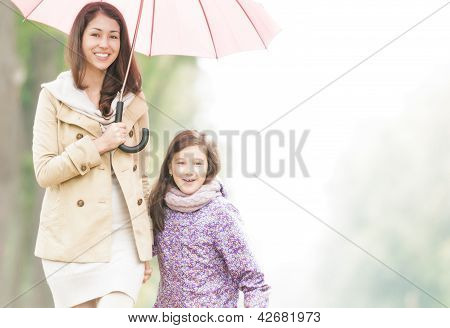 Happy mother and daughter walking in park.