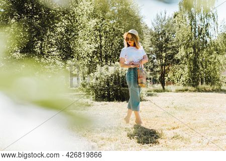 Happy Elegant Young Woman In Glasses, A Hat, A White T-shirt And Trousers With A Handbag Walking Bar