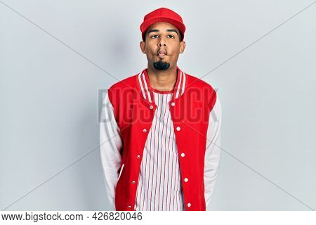 Young african american man wearing baseball uniform making fish face with lips, crazy and comical gesture. funny expression.