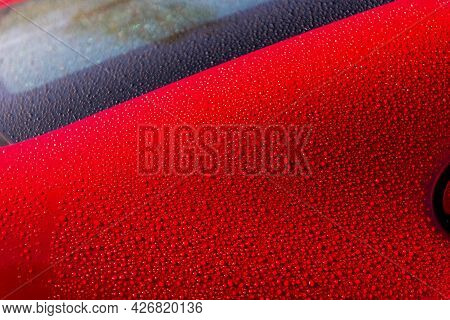 Water Droplet On The Car. Water Beading After Rain Or Car Wash On Red Shiny Paint Surface. Water Dro