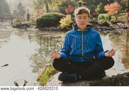 Teenage Boy Meditating And Relaxing In A City Park Japanese Garden. Teen Boy In A Lotus Position Med