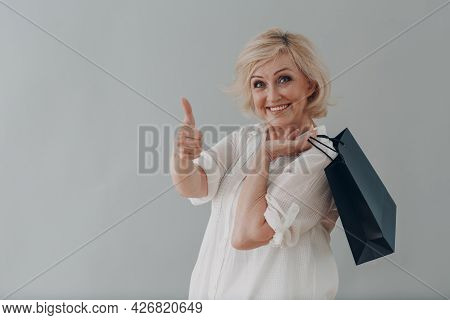 Elderly Caucasian Old Aged Woman Portrait Gray Haired Portrait With Shopping Bags On Gray Background