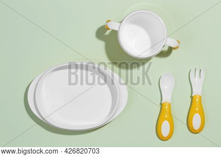 Flat Composition With Plastic Accessories For Baby Food On An Isolated Light Background. The Concept
