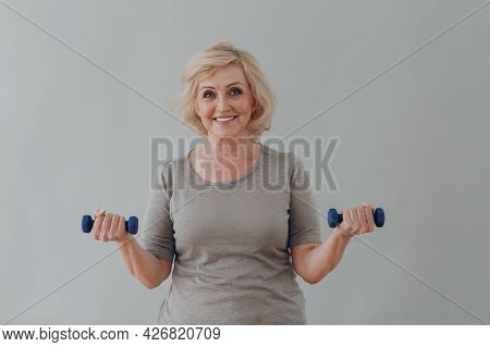 Elderly Caucasian Old Aged Woman Portrait Gray Haired Doing Exercises With Dumbbells On Grey Backgro