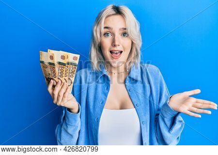 Young blonde girl holding hungarian forint banknotes celebrating achievement with happy smile and winner expression with raised hand