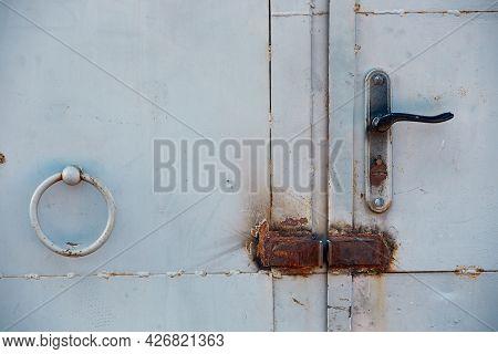 The Handle On The Rusty Iron Garage Door. The Door Handles And Door Latches Are Rusty,natural Light.