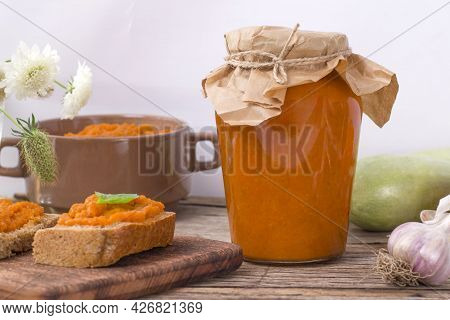 Jar With Squash Caviar And A Sandwich On A Wooden Background. Squash Spread, Zucchini Caviar And Ing