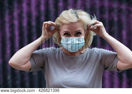 Elderly Woman In Face Mask Put On Outdoor. Old Aged Female Wearing Protective Medical Mask