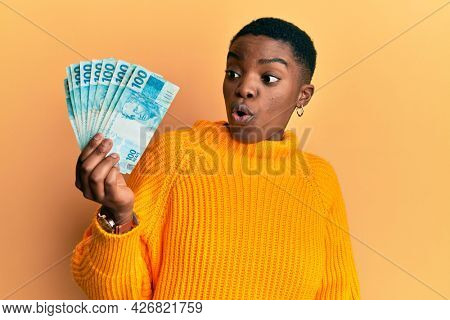 Young african american woman holding 100 brazilian real banknotes scared and amazed with open mouth for surprise, disbelief face