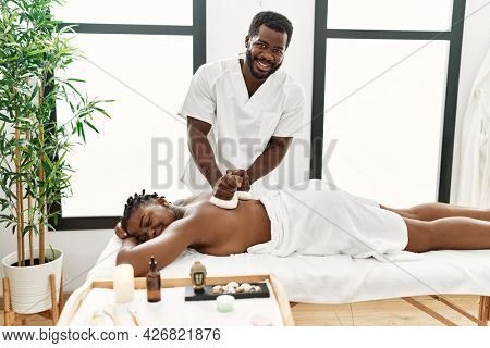 Young african american woman reciving herbal pouches thai massage at beauty center.