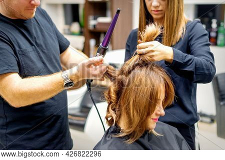 Two Hairstylists Using Curling Iron On Customers Long Brown Hair In A Beauty Salon