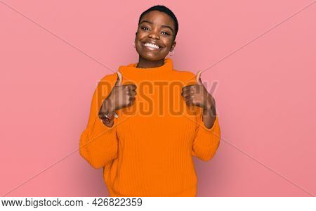 Young african american woman wearing casual clothes success sign doing positive gesture with hand, thumbs up smiling and happy. cheerful expression and winner gesture.