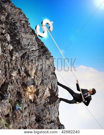 busiessman climbing mountain with dollar on top