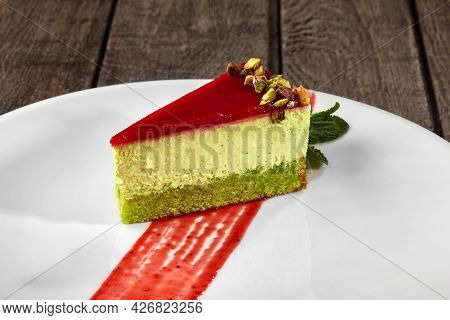 Slice Of Pistachio Cheesecake With Berry Jelly And Chopped Nuts
