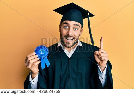 Young hispanic man wearing graduation robe holding 1 st place badge smiling with an idea or question pointing finger with happy face, number one