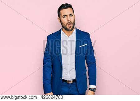 Young hispanic man wearing business jacket in shock face, looking skeptical and sarcastic, surprised with open mouth