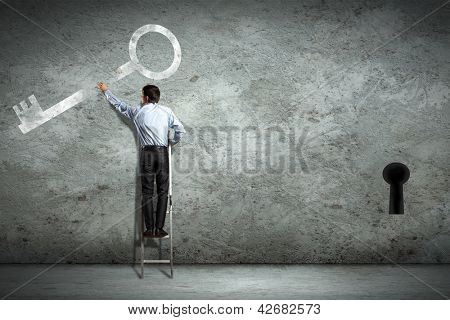 Image of businessman standing on ladder holding key