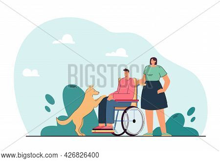 Dog Next To Disabled Man On Wheelchair. Woman Helping Handicapped Person Playing With Domestic Anima