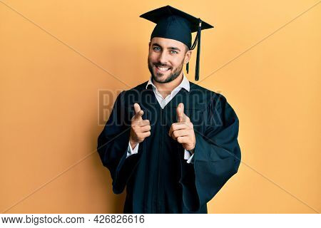 Young hispanic man wearing graduation cap and ceremony robe pointing fingers to camera with happy and funny face. good energy and vibes.