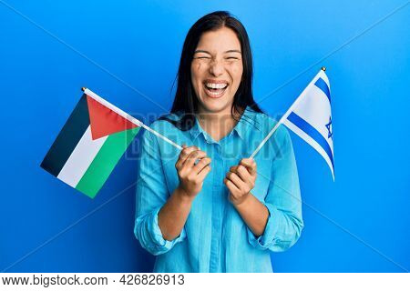 Young latin woman holding palestine and israel flags smiling and laughing hard out loud because funny crazy joke.