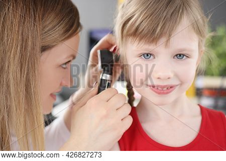 Woman Pediatrician Looking At Eardrum Of Little Girl Using Otoscope In Clinic
