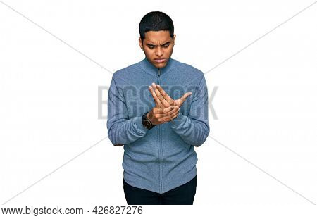 Young handsome hispanic man wearing casual sweatshirt suffering pain on hands and fingers, arthritis inflammation