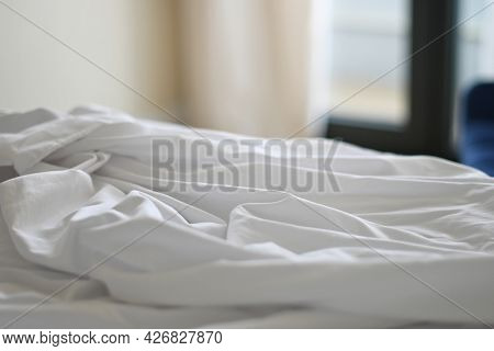 Unmade bed with crumpled bed sheet. Shallow depth of field