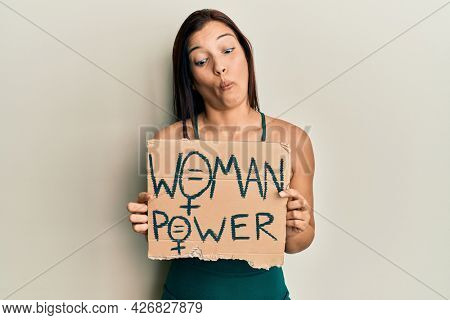 Young latin woman holding woman power banner making fish face with mouth and squinting eyes, crazy and comical.