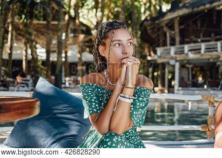 Pensive Woman Sitting Against Poolside In Bali Hotel