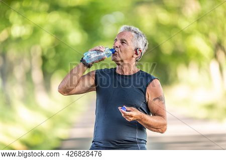 Handsome Elderly Man Rehydrates After A Run Outdoors In The Nature By Drinking Water From A Bottle.