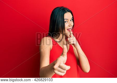 Young hispanic girl wearing casual style with sleeveless shirt pointing fingers to camera with happy and funny face. good energy and vibes.