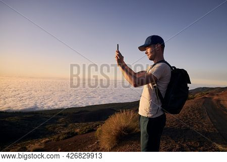 Concentrated Man Photographing Landscape Above Clouds. Tourist Enjoy At Beautiful Sunset. Tenerife,