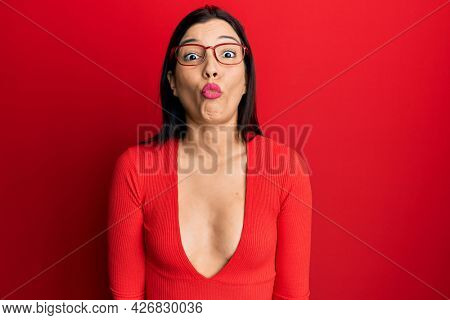 Young latin woman wearing casual clothes and glasses making fish face with lips, crazy and comical gesture. funny expression.