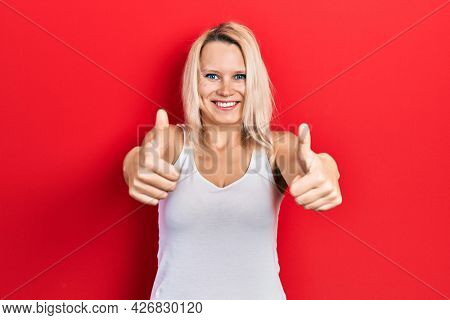 Beautiful caucasian blonde woman wearing casual white t shirt approving doing positive gesture with hand, thumbs up smiling and happy for success. winner gesture.