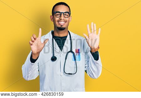 Young african american man wearing doctor uniform and stethoscope showing and pointing up with fingers number seven while smiling confident and happy.