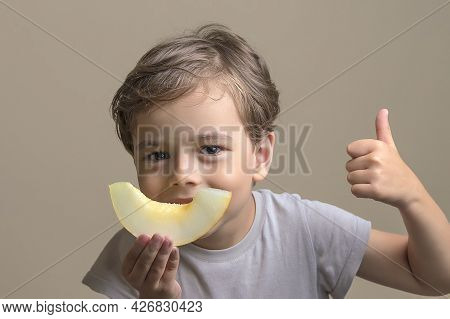 Handsome, Happy Boy Holding Ripe, Sweet, Juicy, Fresh Slice Of Melon And Shows Thumbs Up. Smiling Ch