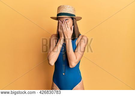 Young brunette girl wearing swimsuit and summer hat rubbing eyes for fatigue and headache, sleepy and tired expression. vision problem