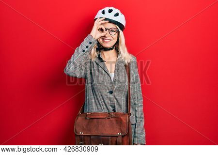 Beautiful caucasian blonde business woman wearing bike helmet doing ok gesture with hand smiling, eye looking through fingers with happy face.