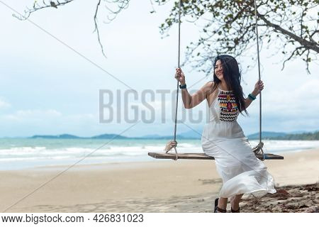 Summer Vacations. Lifestyle Women Relaxing And Enjoying Swing Outdoors Sand Beach, Fashion Stunning