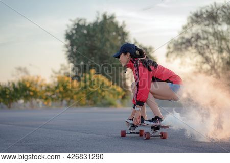 Asian Women Surf Skate Or Skates Board Outdoors On Beautiful Summer Day. Happy Young Women Play Surf