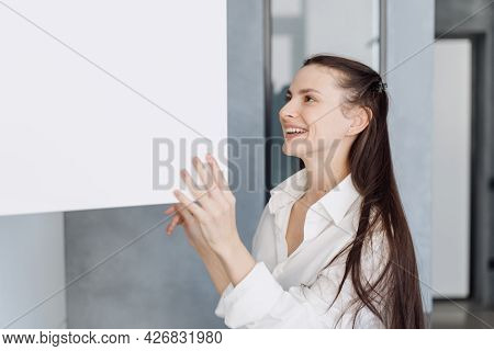 Happy Young Woman In Homewear Smiling While Opening White Cupboard With Clean Dishware While Standin