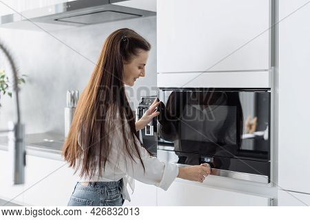 Smiling Beautiful Woman Housewife Preparing Food In Electric Microwave Oven, Adjusting Temperature O